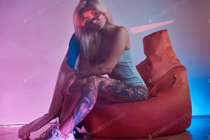 Blond woman is sitting on bean bag