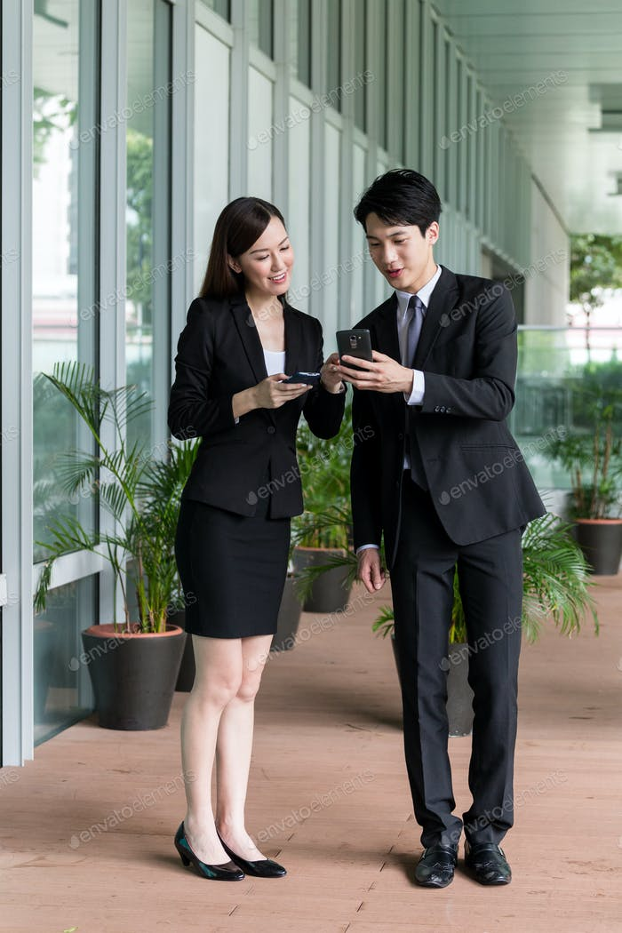 Businesswoman discuss about something on cellphone with businessman