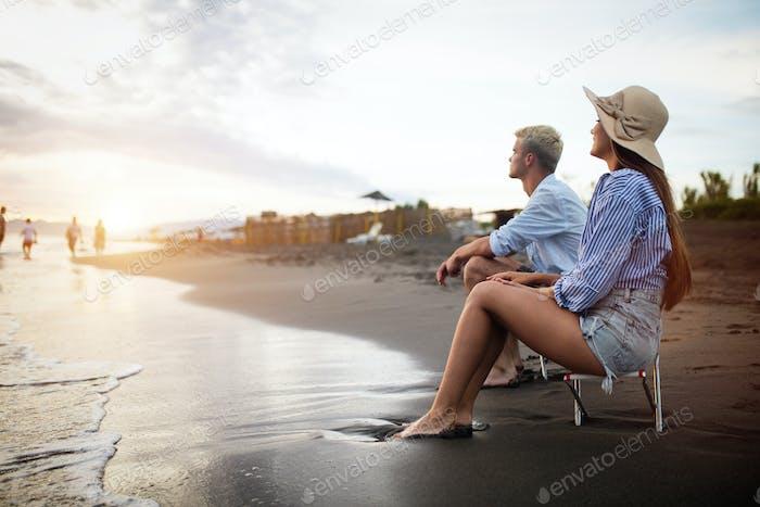 Glückliches junges Paar mit Spaß und Liebe am Strand am sonnigen Tag