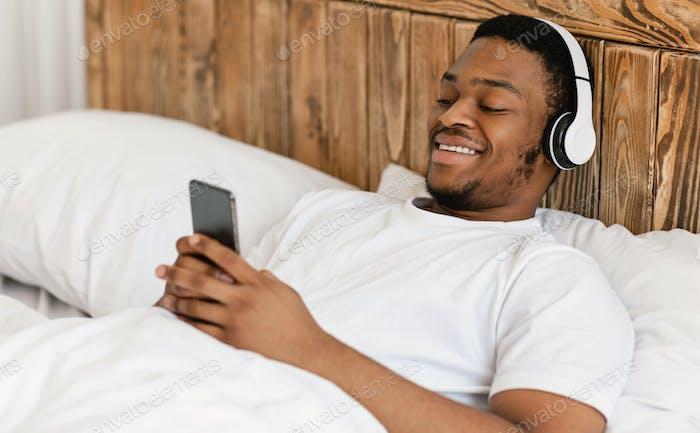 Cheerful Black Guy Using Smartphone Wearing Headphones Lying In Bed