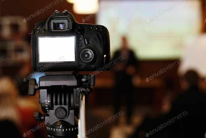 photo video camera with empty white screen in audience  recording