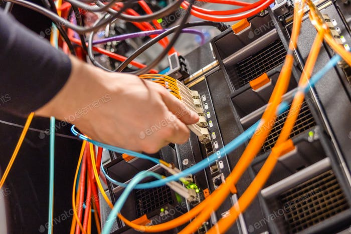 Male Technician Plugging Fiber Channel Network Cable In Blade Server Switch