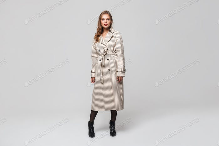 Young beautiful lady with wavy hair in striped coat and black boots dreamily looking in camera