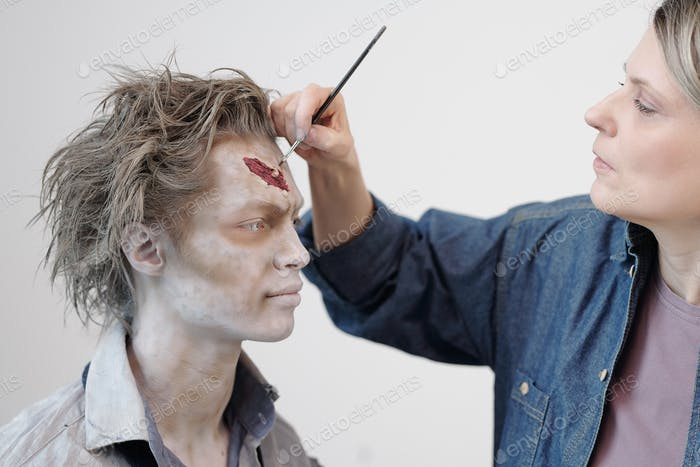 Contemporary visage artist with brush applying zombie makeup on face of young businessman or actor