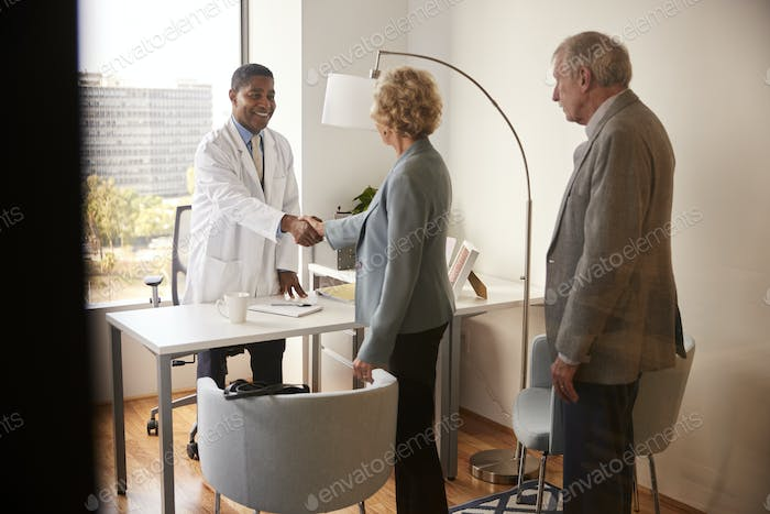 Senior Couple Being Greeted By Male Doctor With Handshake On Visit To Hospital For Consultation