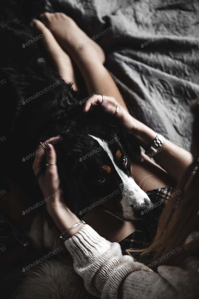 Beautiful girl lying and her cute dog Bernese Mountain Dog on bed, Stylish, fashionable, cozy