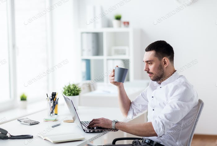 businessman with coffee typing on laptop at office