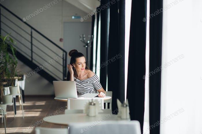 Auf der Suche nach Inspiration. junge schöne nachdenkliche Frau machen einige Notizen und Blick durch Fenster