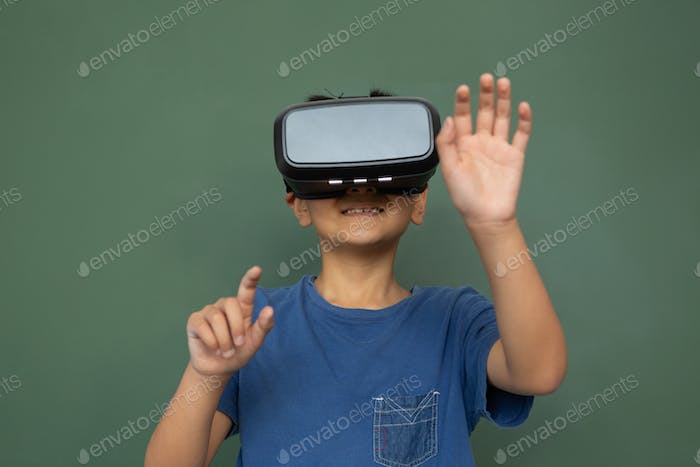 Playful schoolboy using virtual reality headset against greenboard in classroom at elementary school