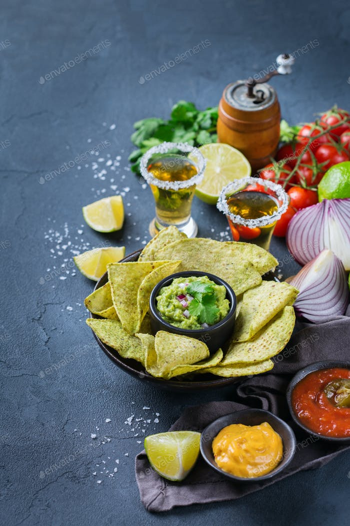 Corn tortilla chips nachos with guacamole, chili, cheese salsa, tequila