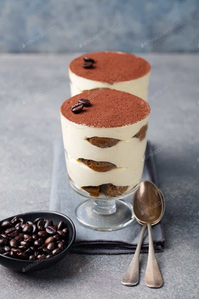 Tiramisu, traditional Italian dessert in glass on a grey stone background.