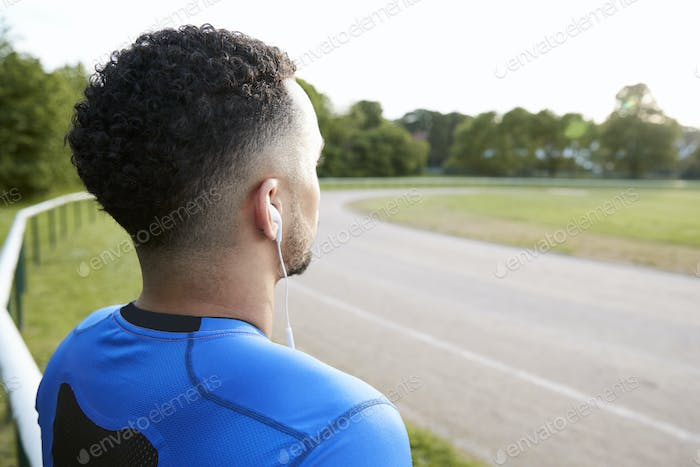 Male athlete at track looking away, close up, back view