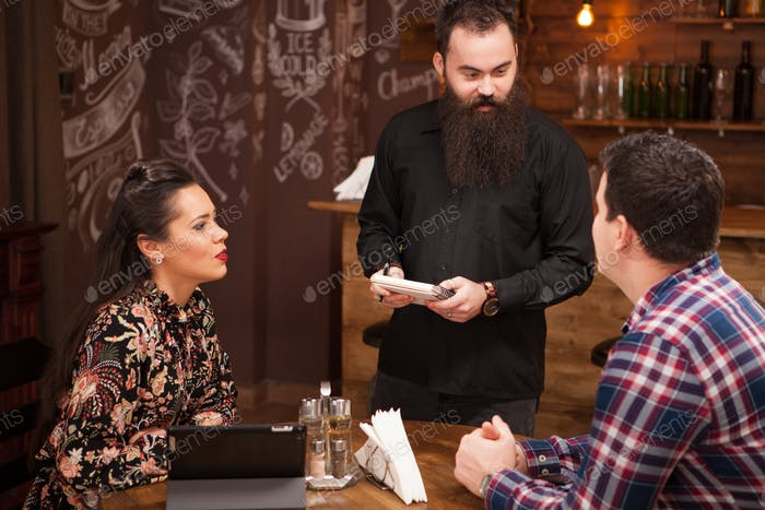 Waiter taking order from stylish couple in restaurant