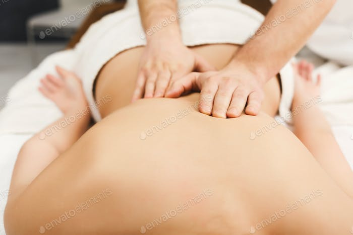 Closeup of hands massaging female shoulders and back