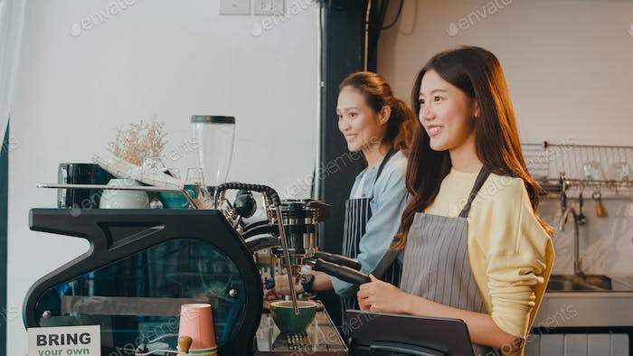 Beautiful young Asia lady barista working with coffee machine in coffee shop.