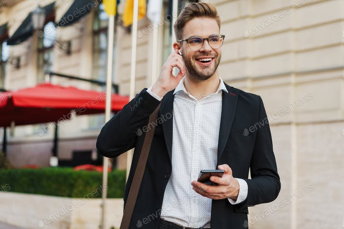 Handsome joyful businessman using wireless earphone and mobile phone