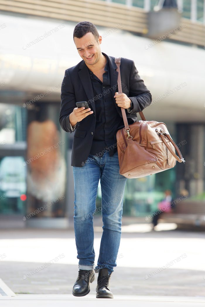 Full body happy man walking in city with bag and cellphone
