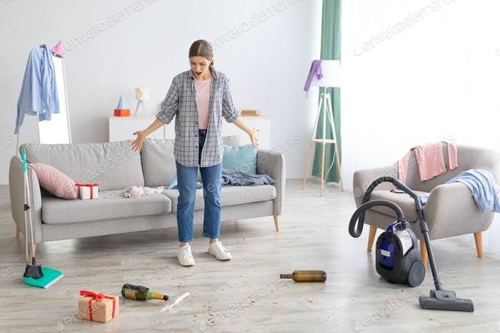 Young woman standing in messy apartment after party, screaming from despair, empty space