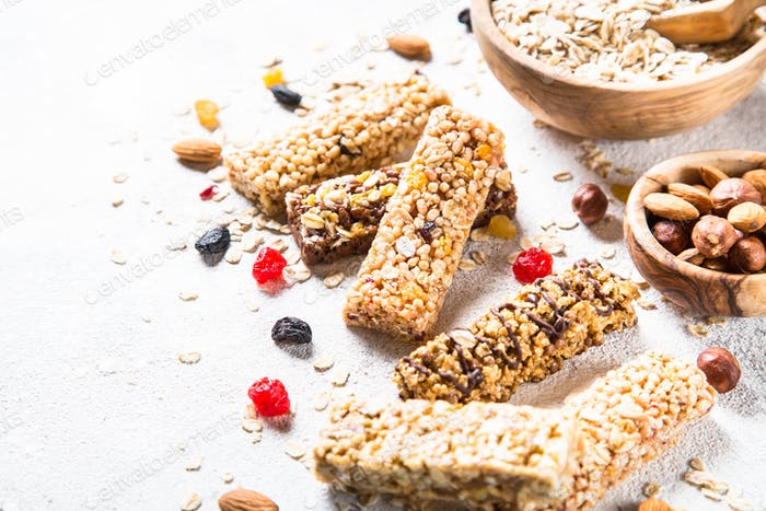 Granola bar with nuts, fruit and berries on white
