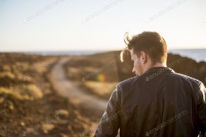 nice beautiful man walk on a desert path alone with nobody around