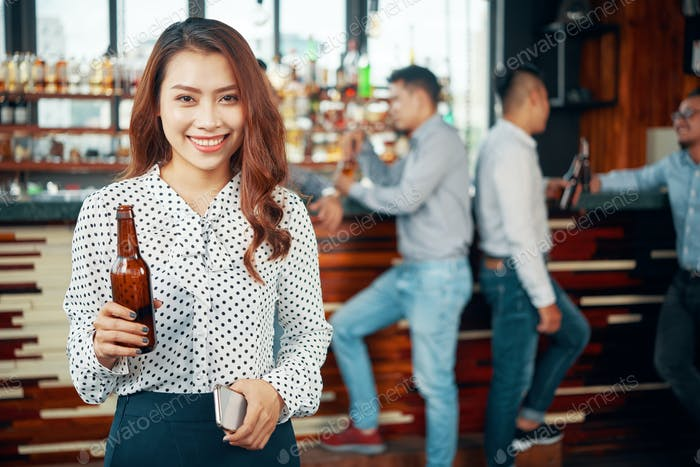 Asian woman drinking beer at pub