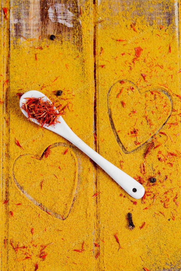 Corazón de especias y condimentos. Cuchara blanca con azafrán sobre Fondo curry.