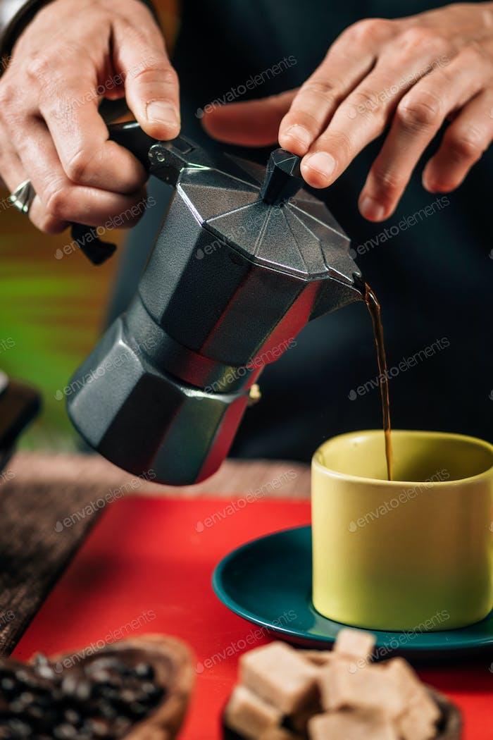 Gießen Kaffee aus einem schwarzen, matten Herd Mokka Topf