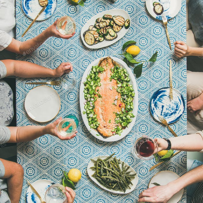 Mediterranean style dinner with cooked salmon, bread, lemonade, square crop