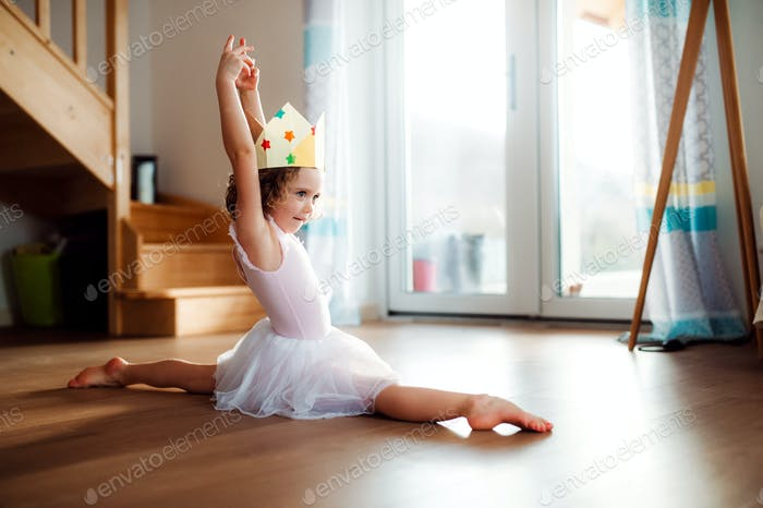A small girl with a princess crown at home, doing gymnastic split.