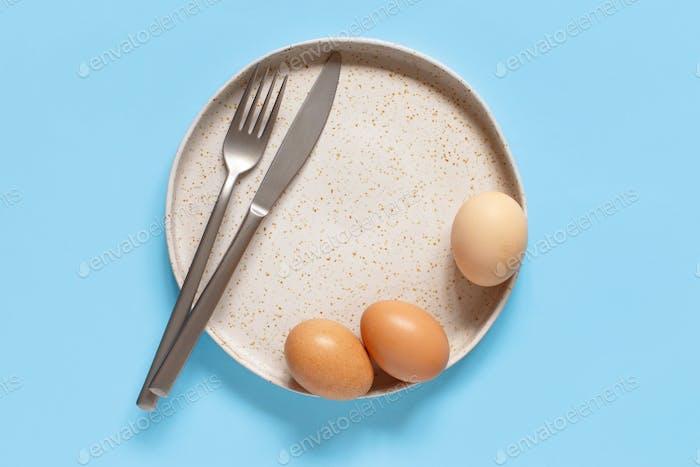 Plate, eggs, fork and knife over light blue background