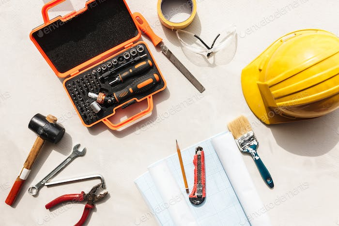 Close up yellow hardhat and repair tools over white background i