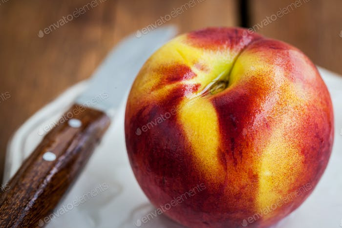 Fresh ripe peach on plate, wooden background, selective focus