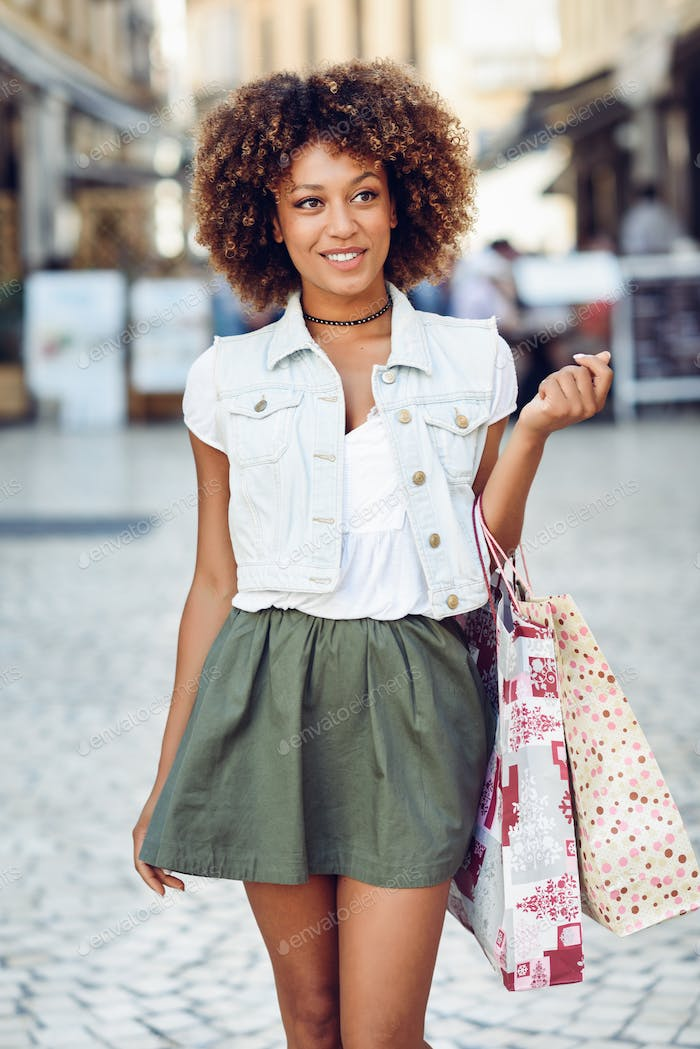 Black woman, afro hairstyle, with shopping bags in the street.
