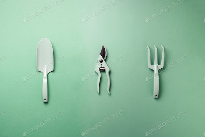 Gardening tools and utensils on green background. Top view with copy space. Pruner, rake, shovel for