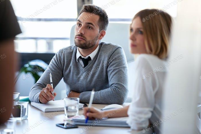 Konzentriertes Business-Team hört sie Partner auf Coworking Space.