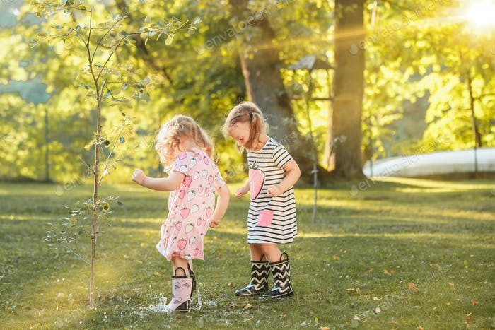 The cute little blond girls in rubber boots playing with water splashes on the field in summer