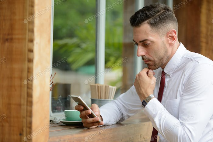 Portrait of businessman thinking while using phone at the coffee shop