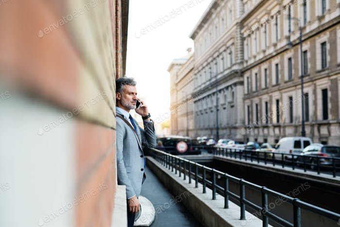 Mature businessman with smartphone in a city.