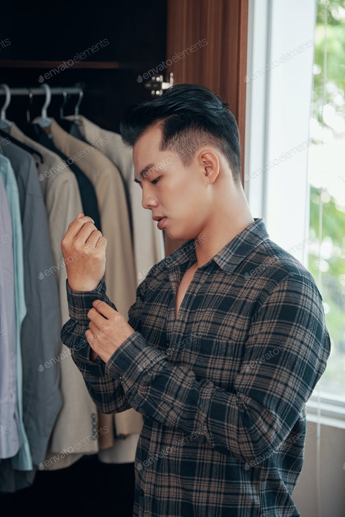 Young ethnic man dressing at home