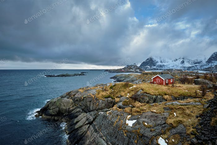 Clif with traditional red rorbu house on Lofoten Islands, Norway