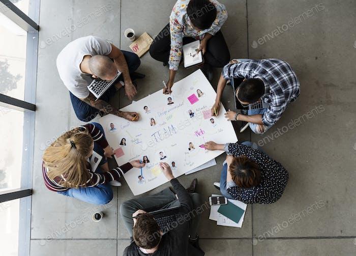 Group of people brainstorming sitting on the floor