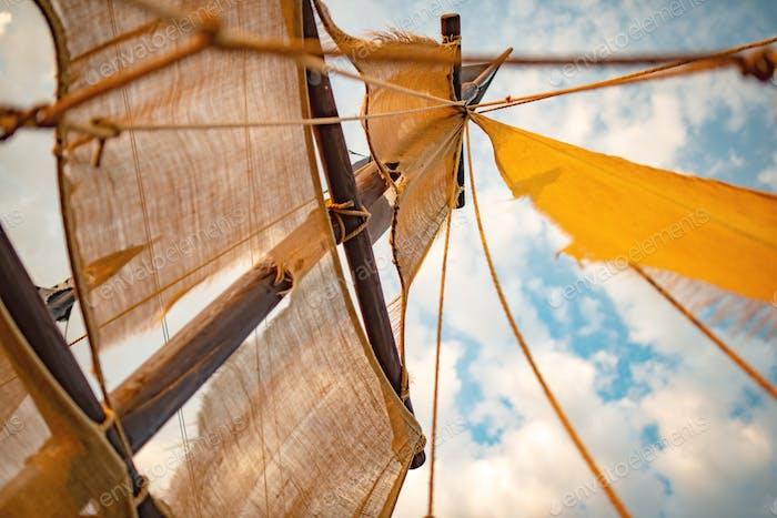 Unteransicht eines Schiffmast mit beigefarbenen Segeln