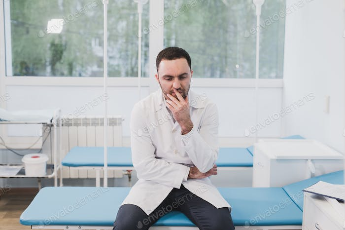 Thoughtful doctor sitting in a operating room with his hand on head