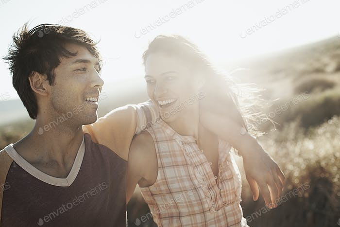 A young couple side by side in the desert, laughing.