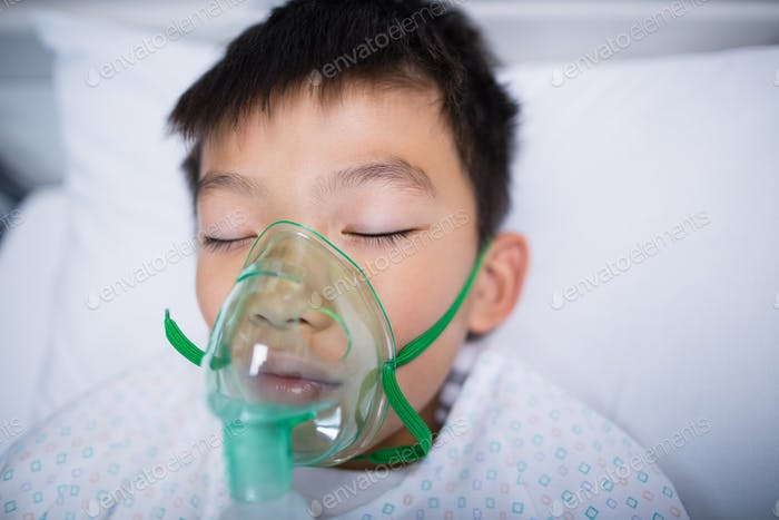 Boy patient wearing oxygen mask lying on hospital bed