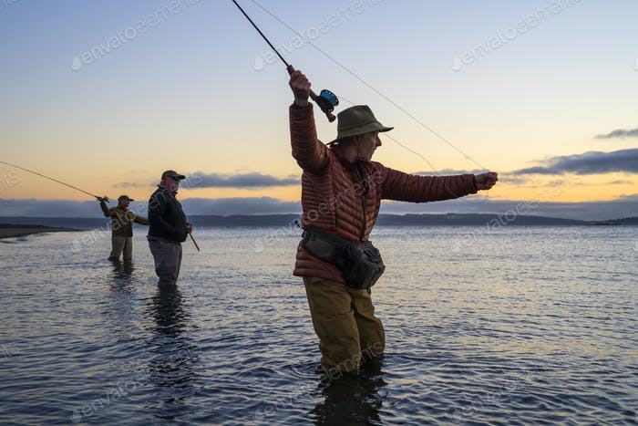 Two fly fishermen cast for searun coastal cutthroat trout and salmon with their guide standing