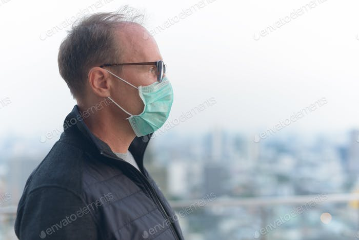 Profile view of mature man with mask for protection from corona virus outbreak and pollution in the