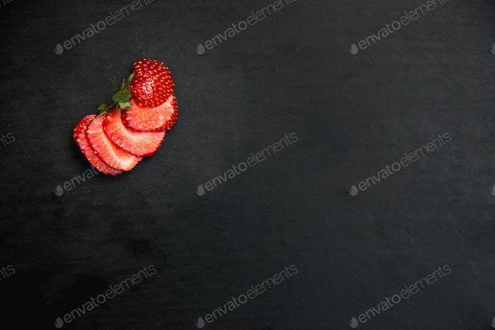 Draufsicht eine geschnittene Erdbeere auf schwarzem Holzhintergrund