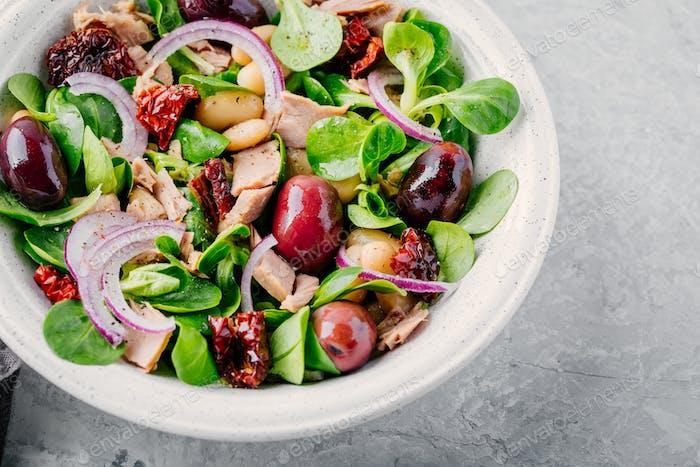Salat mit weißen Bohnen, Thunfisch, Oliven, roten Zwiebeln und getrockneten Tomaten mit grünen Salatblättern