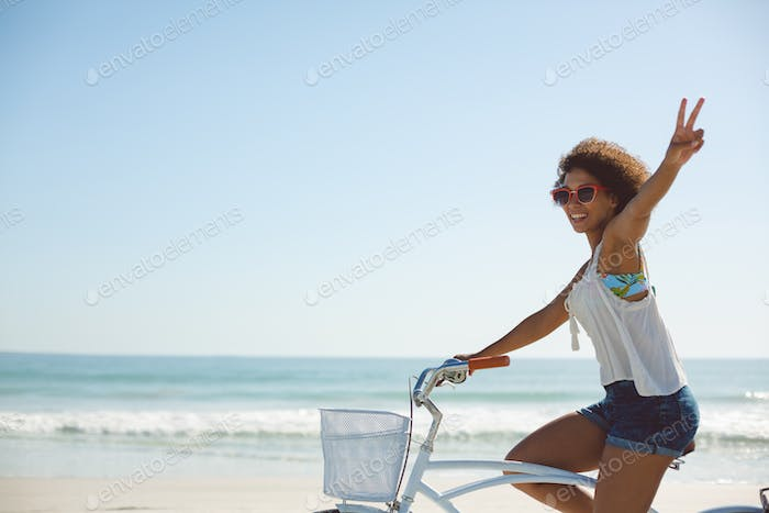 Beautiful African american woman showing victory sign while riding a bicycle